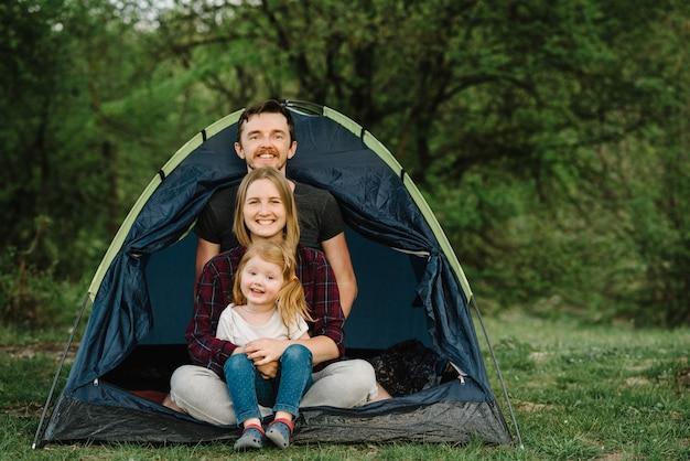 Wesołych rodzinnych wakacji w namiocie z dzieckiem na łonie natury. matka, ojciec przytula dziecko i spędzają wakacje na kempingu na wsi. koncepcja wakacji i podróży, podróży. obozowisko.