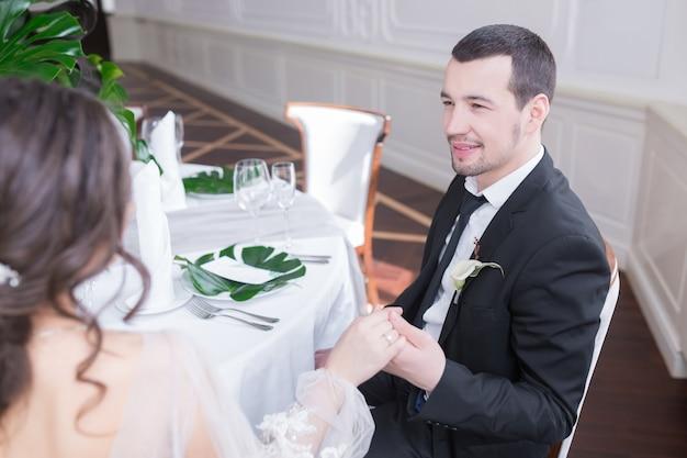Wesołych stylowych bradi i pana młodego świętującego wesele w sali restauracyjnej