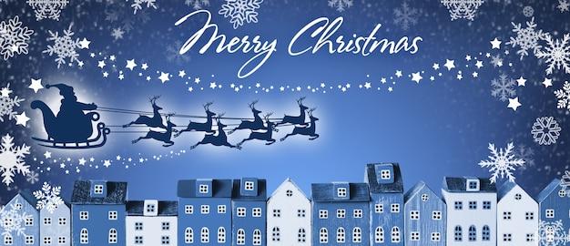Wesołych świąt bożego narodzenia banner - święty mikołaj w saniach i reniferach leci nad domami miasta na niebieskim tle zimowego.