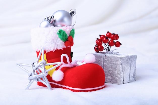 Wesołych świąt bożego narodzenia. buty świętego mikołaja z pudełkami na upiornych piórach ze śniegiem i płatkami śniegu.