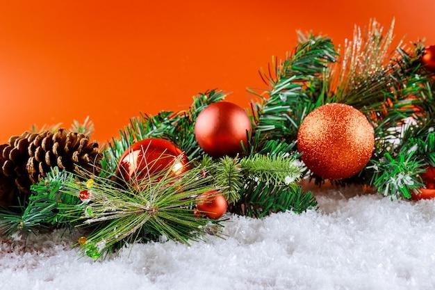 Wesołych świąt bożego narodzenia dekoracje śniegowe na gałęzi jodły z szyszkami, płatki śniegu w bombkach