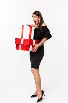 Wesołych świąt bożego narodzenia i nowego roku koncepcja wakacje. pełna długość kobiety, patrząc zdziwiona prezentami świątecznymi, odbiera prezenty, stojąc zdziwiona na białym tle.
