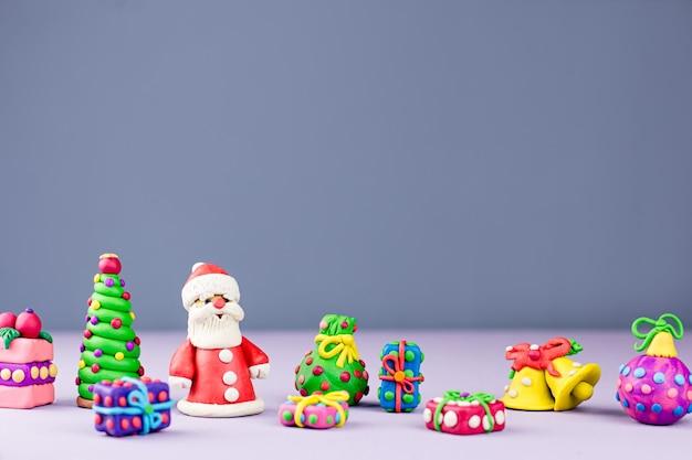 Wesołych świąt bożego narodzenia kartkę z życzeniami z dekoracjami. święty mikołaj, choinka i prezenty