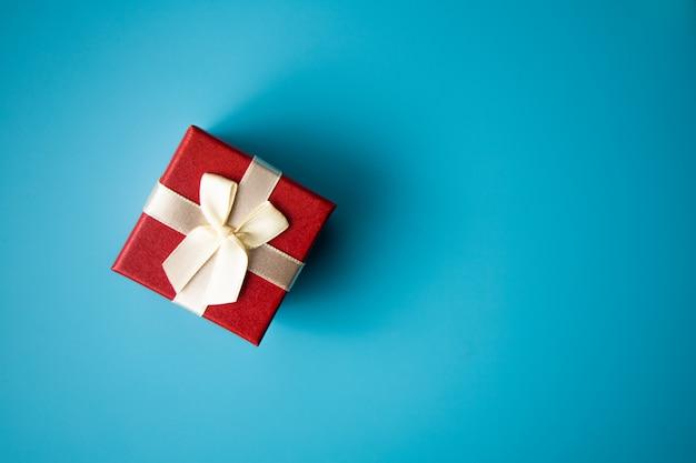 Wesołych świąt bożego narodzenia koncepcja: czerwone pudełko na niebieskim tle