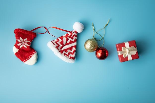 Wesołych świąt bożego narodzenia koncepcja: czerwone pudełko obecne i czerwone dziecko noworodka skarpety i kapelusz na niebieskim tle