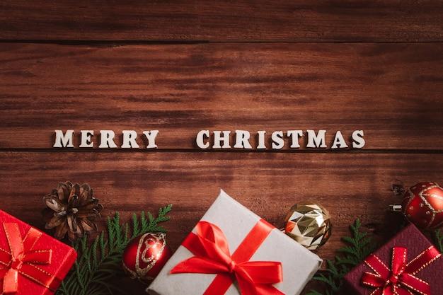 Wesołych świąt bożego narodzenia koncepcja. piękne pudełka na prezenty i gałęzie jodły na tle drewnianych.