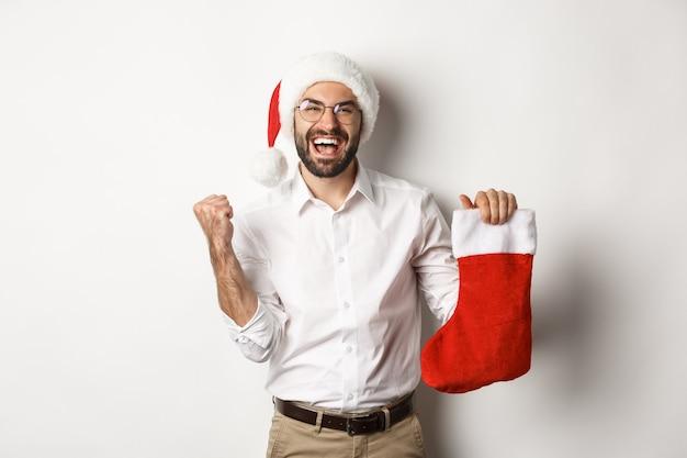 Wesołych świąt bożego narodzenia, koncepcja wakacji. szczęśliwy dorosły człowiek otrzymuje prezenty w skarpetce bożonarodzeniowej, patrząc podekscytowany, w kapeluszu mikołaja
