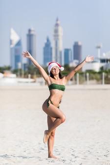 Wesołych świąt bożego narodzenia. młoda dziewczyna szczęśliwa z radości i zaskoczenia na idealnej białej, piaszczystej plaży na ferie zimowe. młoda kobieta jest ubranym santa kapeluszowe ręki podnosić szczęście podczas wakacji.