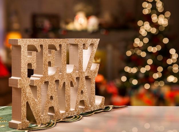 Wesołych świąt bożego narodzenia pozdrowienie wiadomość na podłoże drewniane. wesołych świąt napisane w języku portugalskim. feliz natal.
