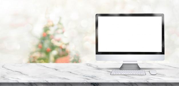 Wesołych świąt bożego narodzenia transparent, makiety komputer stacjonarny na biały marmurowy stół z rozmycie choinki