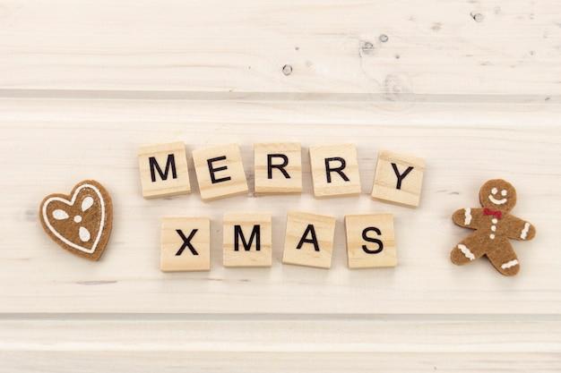 Wesołych świąt bożego narodzenia z piernik i drewniane litery tekstu na jasnym tle
