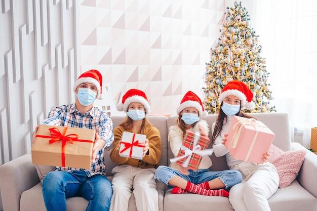 Wesołych świąt. czteroosobowa rodzina z prezentami na boże narodzenie. rodzice i dzieci noszą maski na twarz