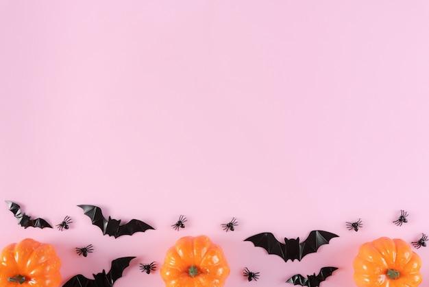 Wesołych świąt halloween z cukierek albo psikus, dynie, cukierki i pająki na pastelowym różowym tle.