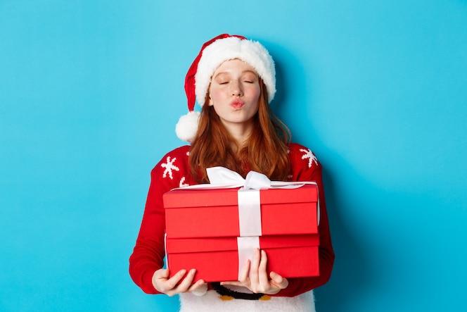 Wesołych świąt i koncepcji bożego narodzenia. ładna ruda dziewczyna trzyma prezenty i marszczy się usta do pocałunku, nosi czapkę santa i zabawny sweter, niebieskie tło.