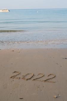Wesołych świąt i nowego roku 2022 w piaszczystej liczbie na brzegu morza na niebieskim tle oceanu