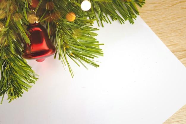 Wesołych świąt i szczęśliwego nowego roku 2021 koncepcja, zbliżenie złote dzwony zwisające z udekorowanego drzewa z bokeh, tło wakacje boże narodzenie. list do świętego mikołaja.