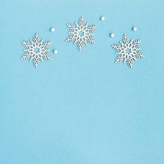 Wesołych świąt i szczęśliwego nowego roku kartkę z życzeniami z drewnianymi płatkami śniegu na niebieskim tle