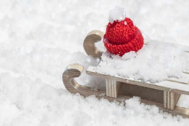 Wesołych świąt i szczęśliwego nowego roku kartkę z życzeniami z drewnianymi saniami i czerwoną czapkę boże narodzenie na tle śniegu z miejsca kopiowania. selektywne ustawianie ostrości.