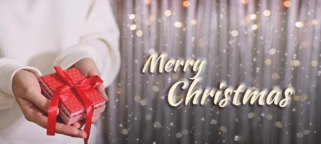 Wesołych świąt i szczęśliwego nowego roku kobieta w białym swetrze trzymająca prezenty świąteczne