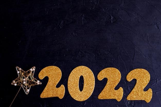 Wesołych świąt i szczęśliwego nowego roku koncepcja 2022 złote cyfry na czarnym tle