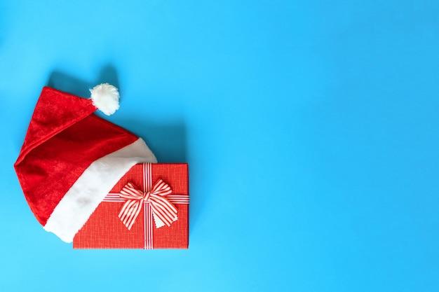Wesołych świąt i szczęśliwego nowego roku koncepcja. boże narodzenie czerwony prezent ozdobiony czerwoną wstążką w czapce świętego mikołaja na białym tle na niebieskim tle, miejsce. może służyć jako kartka świąteczna