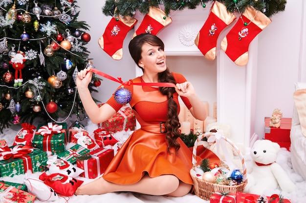 Wesołych świąt i szczęśliwego nowego roku! młoda kobieta z teraźniejszości pudełkiem i prezentami przy boże narodzenie dekorującym domem