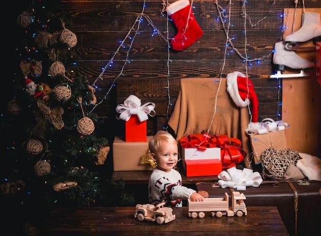 Wesołych świąt i szczęśliwego nowego roku. śliczna mała dziewczynka dekoruje choinkę w pomieszczeniu. dostawa prezentów świątecznych.
