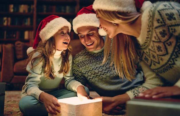Wesołych świąt i szczęśliwego nowego roku!szczęśliwa rodzina czeka na nowy rok w czapkach świętego mikołaja. rodzice prezentują swojej uroczej córce pudełko upominkowe. magiczne światło od środka.
