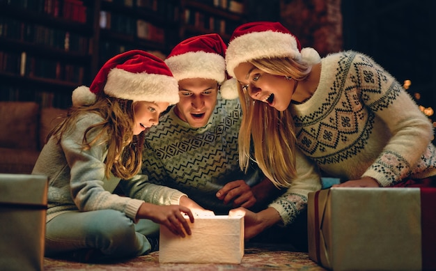 Wesołych świąt i szczęśliwego nowego roku! szczęśliwa rodzina czeka na nowy rok w czapkach świętego mikołaja. rodzice prezentują uroczej córce pudełko.