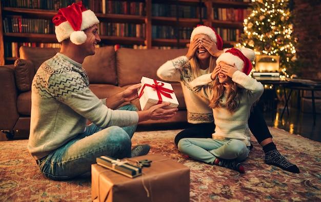 Wesołych świąt i szczęśliwego nowego roku! szczęśliwa rodzina czeka na nowy rok w czapkach świętego mikołaja, wymieniając się prezentami.