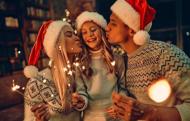 Wesołych świąt i szczęśliwego nowego roku! szczęśliwa rodzina świętuje ferie zimowe w domu. rodzice z córką czekają na boże narodzenie w czapkach mikołaja z ogniami w dłoniach.