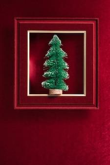 Wesołych świąt i szczęśliwego nowego roku tekst i choinka w filcowej ramce na aksamitny czerwony filc