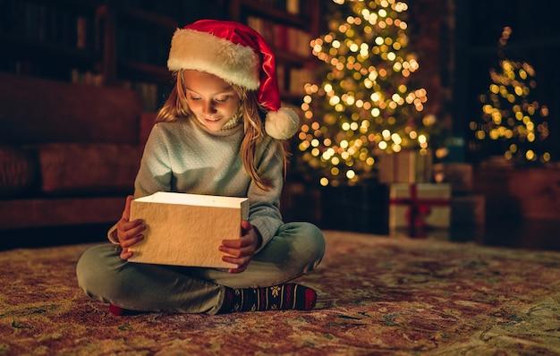 Wesołych świąt i szczęśliwego nowego roku! urocza mała dziewczynka siedzi w domu z otwartym pudełkiem. magiczne światło z wnętrza.
