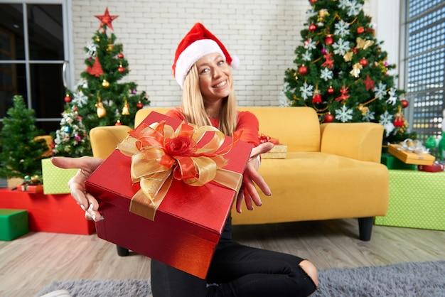 Wesołych świąt i szczęśliwego nowego roku wakacje, piękna biała kaukaska kobieta świętują, wymieniając prezenty relaksują się przed żółtą sofą i choinką w pokoju
