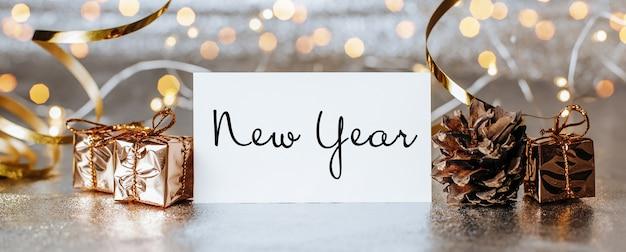 Wesołych świąt i wesołego nowego roku koncepcja z pudełkami prezentowymi i kartką z życzeniami z tekstem nowy rok