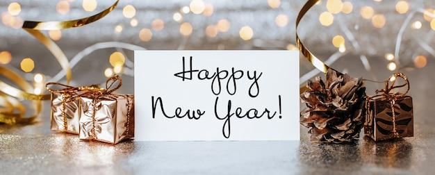 Wesołych świąt i wesołego nowego roku koncepcja z pudełkami prezentowymi i kartką z życzeniami z tekstem szczęśliwego nowego roku