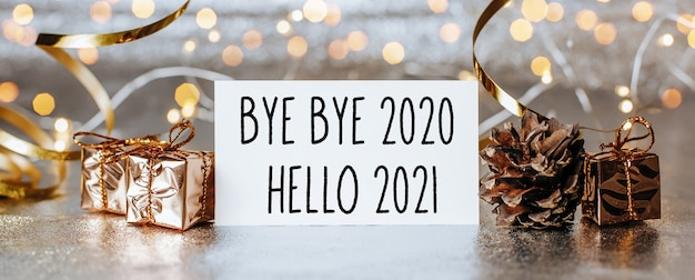 Wesołych świąt i wesołego nowego roku z pudełkami na prezenty i kartką z życzeniami z tekstem bye bye 2020 hello 2021