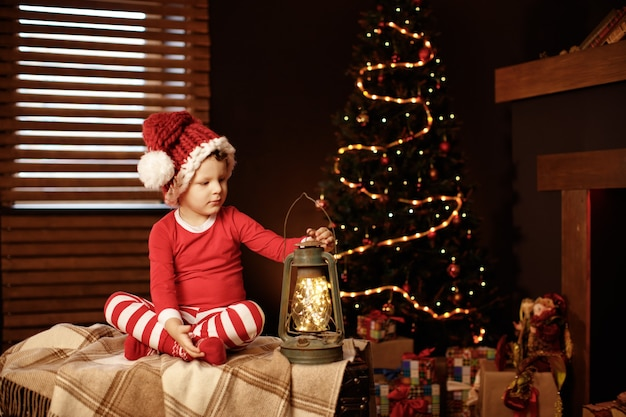 Wesołych świąt i wesołych świąt mały chłopiec siedzi z latarnią na choince nowy rok, elfie.