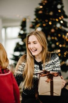 Wesołych świąt i wesołych świąt mama daje córce prezent przy choince