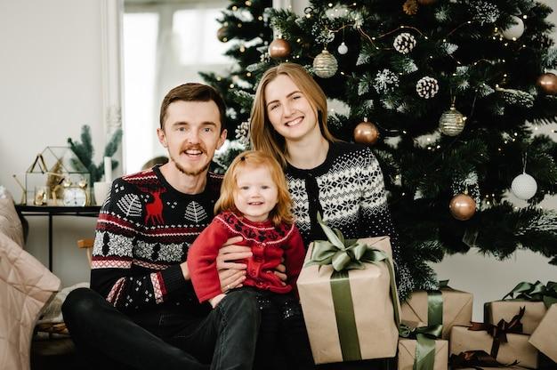 Wesołych świąt i wesołych świąt mama tata daje córce prezent przy choince