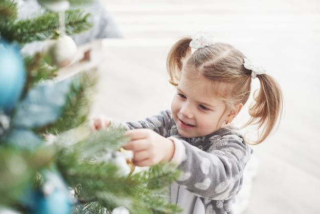 Wesołych świąt i wesołych świąt! młoda dziewczyna pomaga dekorowanie choinki, trzymając w ręku bombki