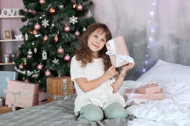 Wesołych świąt i wesołych świąt! nowy rok 2020! koncepcja dzieci, rodziny oraz dzieciństwa i wakacji. dziewczyna w piżamie trzyma prezent noworoczny na tle drzewa noworocznego. świąteczne wnętrze.