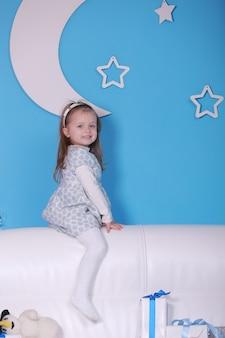 Wesołych świąt i wesołych świąt. nowy rok . portret dziewczynki na białej kanapie z prezentami świątecznymi. koncepcja wakacje nowy rok. niebieska ściana z białym księżycem na ścianie.