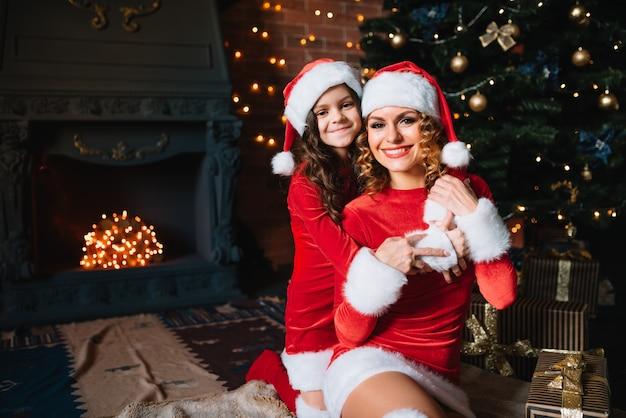 Wesołych świąt i wesołych świąt! piękna mama z córeczką w strojach bożonarodzeniowych spędzają razem czas w pobliżu choinki.