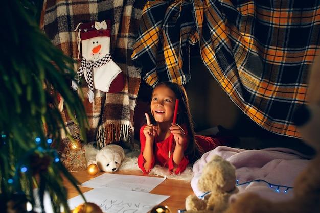 Wesołych świąt i wesołych świąt. śliczne małe dziecko dziewczynka pisze list do świętego mikołaja w pobliżu choinki