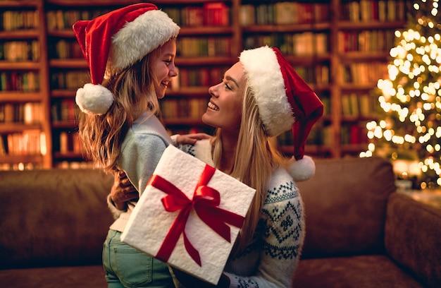 Wesołych świąt i wesołych świąt! wesoła mama i jej śliczna córeczka wymieniają prezenty. rodzic i małe dziecko, zabawy w pobliżu drzewa w pomieszczeniu. kochająca rodzina z prezentami w pokoju.