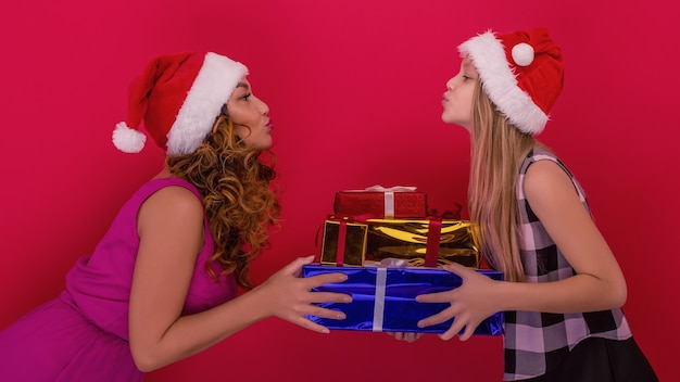 Wesołych świąt i wesołych świąt. wesoła mama i jej urocza córka trzyma prezent na boże narodzenie
