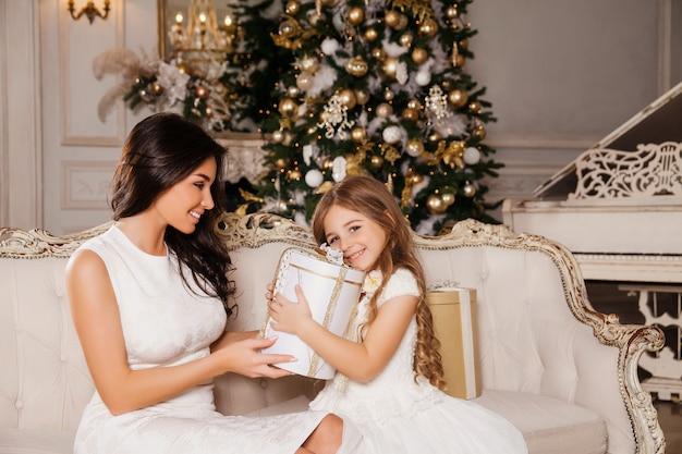 Wesołych świąt i wesołych świąt. wesoła mama i jej urocza córka wymieniają prezenty w białym klasycznym fortepianie i ozdobionej choince. nowy rok