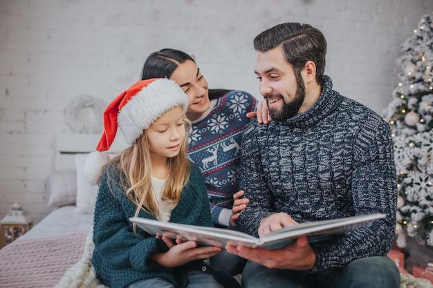 Wesołych świąt i wesołych świąt wesoła mama, tata i jej urocza córka czytają książkę. rodzic i małe dziecko ma zabawę blisko choinki w pomieszczeniu. poranne boże narodzenie. portret rodziny z bliska