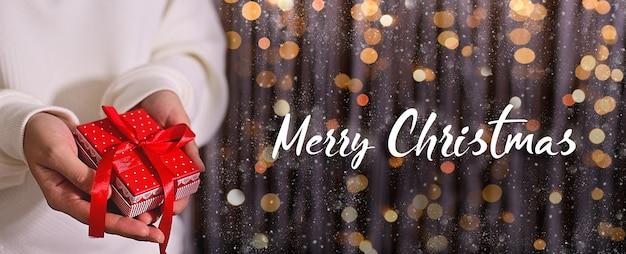 Wesołych świąt kobieta trzymając się za ręce czerwone pudełko na błyszczącym tle z bokeh śniegu i światła